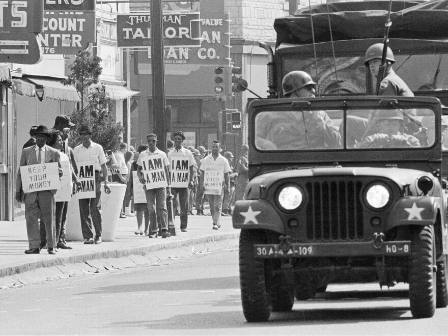 Tennessee National Guard troopers in jeeps and trucks escort a protest march by striking sanitation workers through downtown Memphis, March 30, 1968.