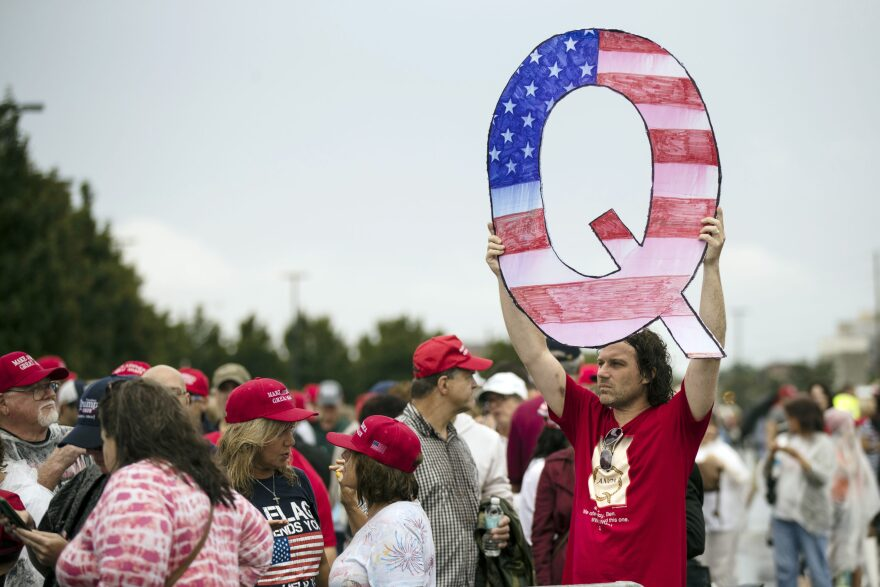 In this Aug. 2, 2018 file photo, David Reinert holding a Q sign waits in line with others to enter a campaign rally with President Donald Trump in Wilkes-Barre, Pa. (Matt Rourke, File/AP)