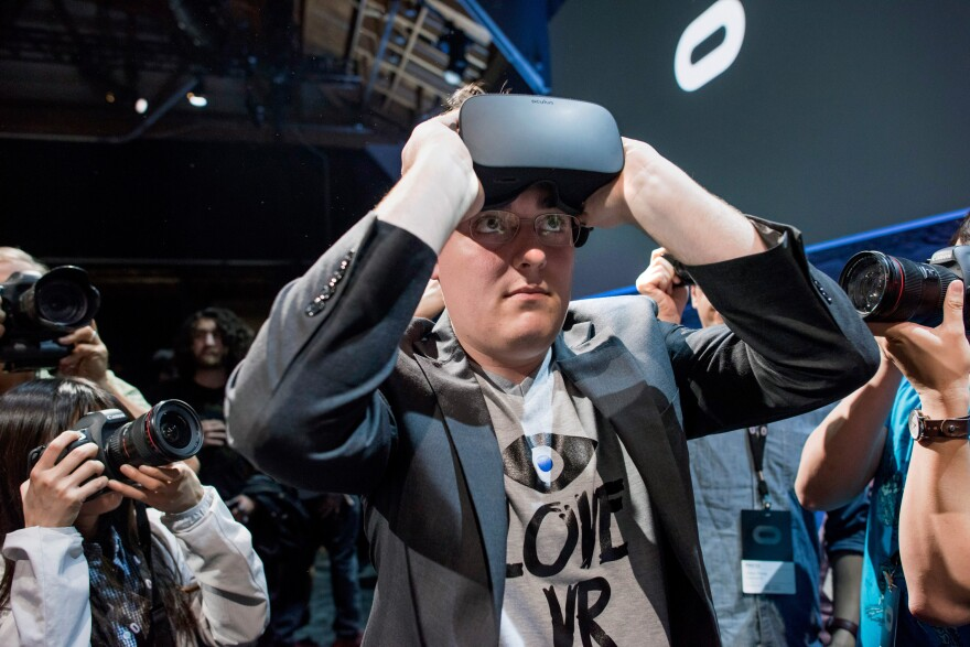 "Palmer Luckey, founder of Oculus VR, demonstrates the new Oculus Rift headset during the ""Step Into The Rift"" event in San Francisco in June 2015."