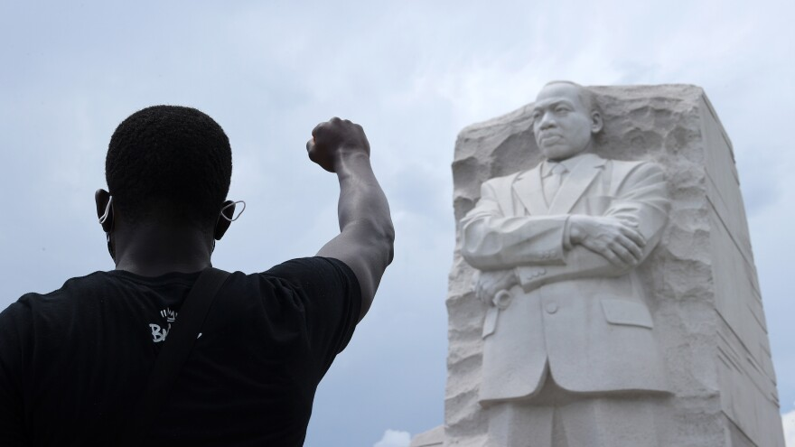 A man kneels and raises his fist in the air during a march and protest to mark the Juneteenth holiday at the Martin Luther King Jr. Memorial June 19, 2020 in Washington, DC.
