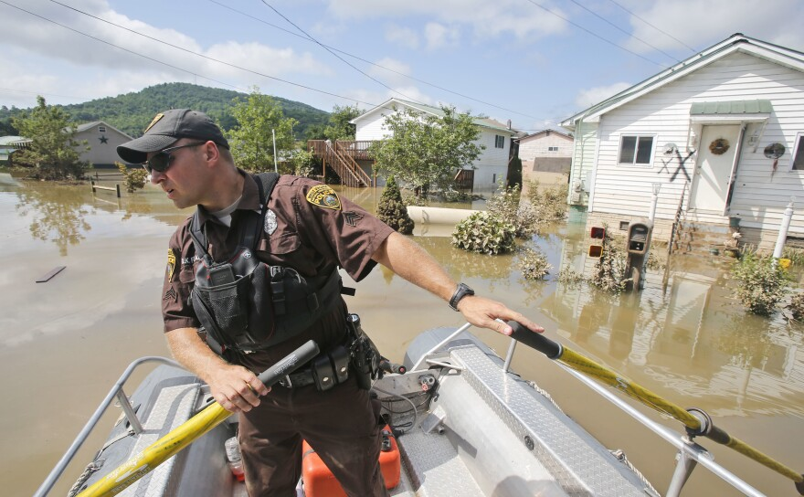 Lt. Dennis Feazell, of the West Virginia Department of Natural Resources, watches for debris as he and a co-worker search flooded homes in Rainelle, W.Va., Saturday, June 25, 2016.