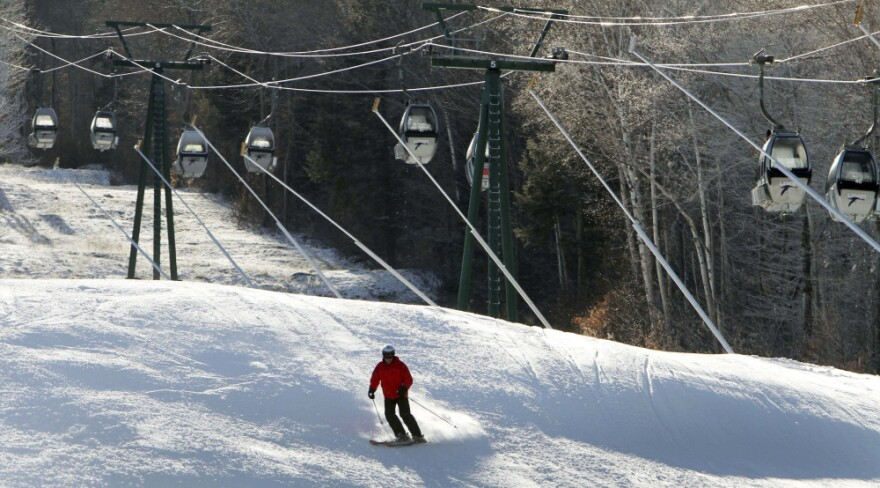 Empty gondolas sit parked above a lone skier in mid-December on an open trail at Loon Mountain ski area in Lincoln, N.H. Warm temperatures have continued to hover above optimal snowmaking levels, making for a late start to the ski season in the Northeast.