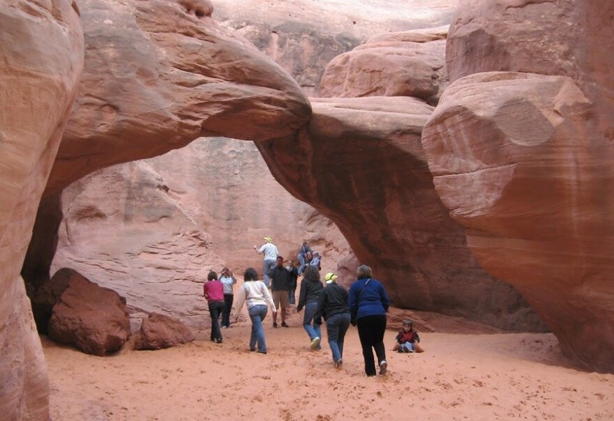 A group of around 10 people gather under a red rock arch.