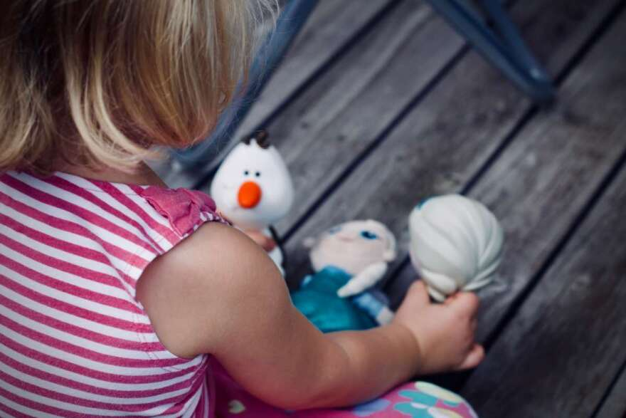 girl playing with stuffed toys