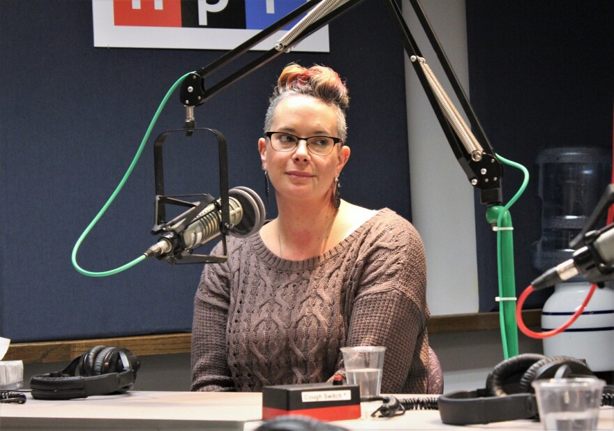 A person sits by a microphone in the KCUR talk show studio.
