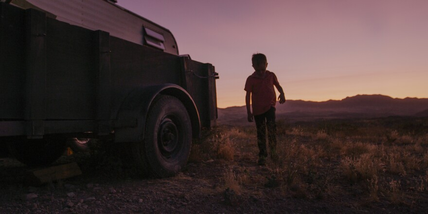 Photo of a boy walking in the desert at sunset.