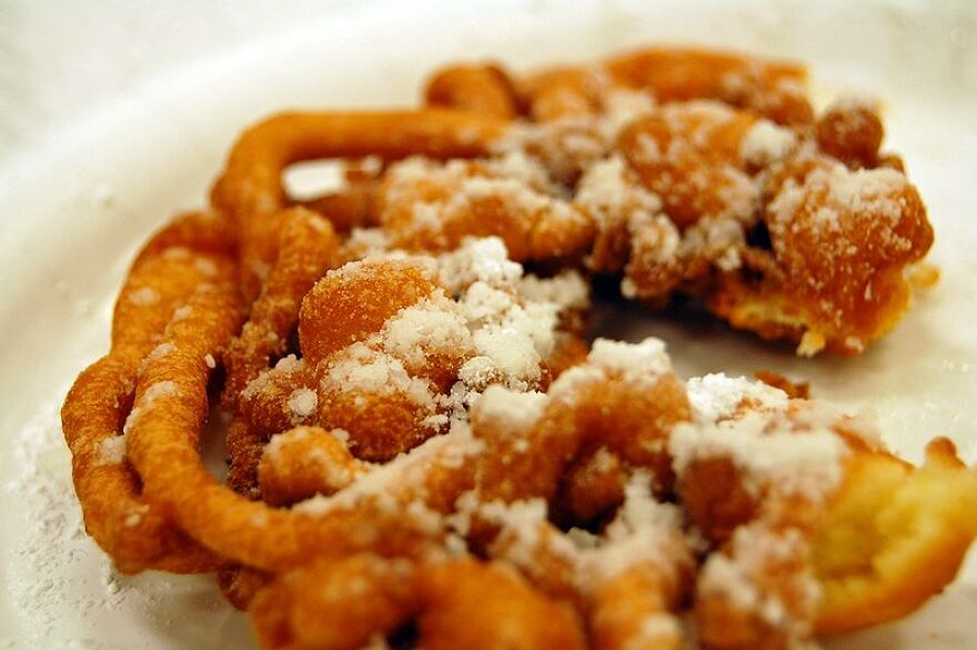 A piece of funnel cake, dusted in powdered sugar.