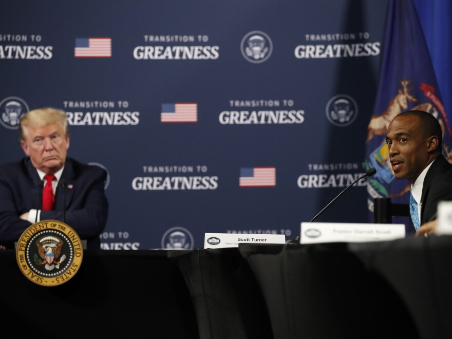 President Trump listens as Scott Turner, executive director of the White House Opportunity and Revitalization Council, speaks during a meeting with African American leaders in Michigan on Thursday.