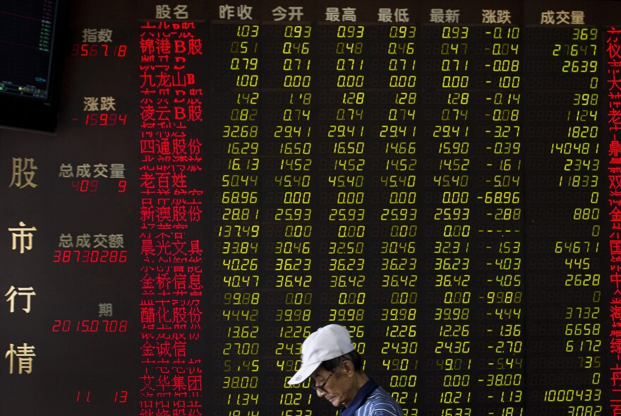 A man walks past an electric board displaying stock prices at a brokerage house in Beijing, China, on Wednesday.