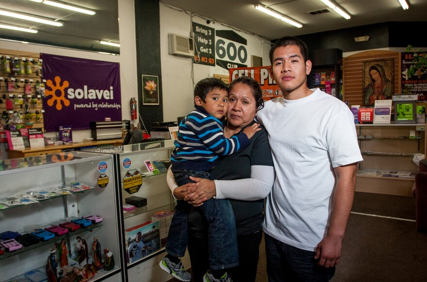 Diego Lobaton stands with his mother, Hedy Julca, and her son, Bruce, inside their cellphone store. Lobaton, Julca and Lobaton's brother Luis were arrested last year after San Diego police stopped the brothers on the suspicion they were breaking into the store.