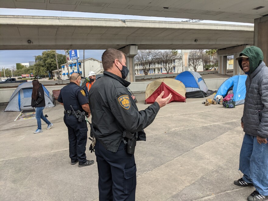 San Antonio police officers talk to Tomanique Grant, who has been camping underneath I-35 for almost a year. | Paul Flahive