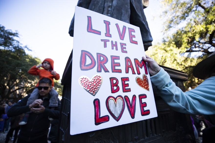 "Martin Luther King Jr. marcher holds sign saying ""Live the Dream, Be Love"""