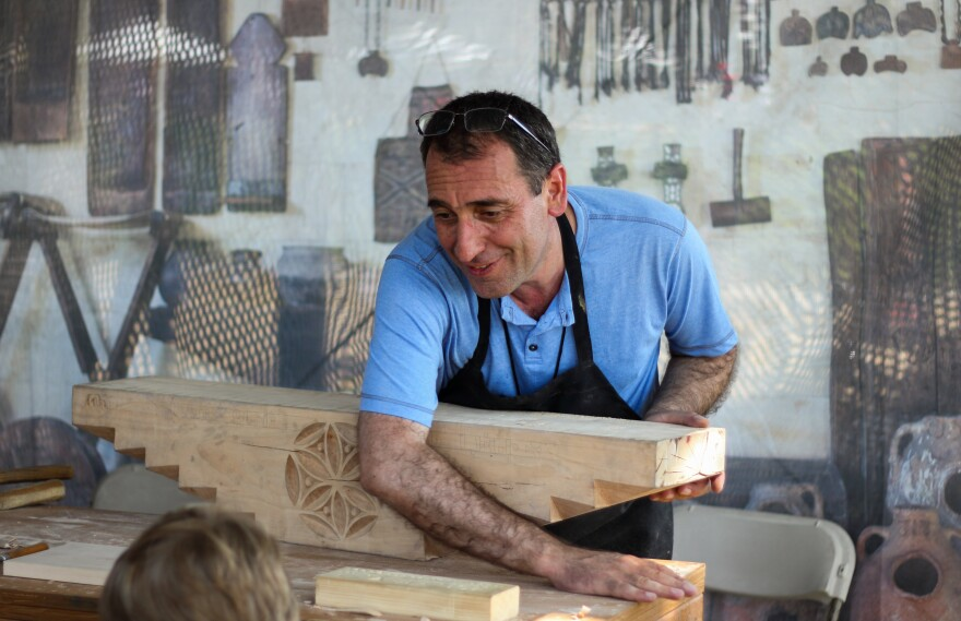 """At the Smithsonian Folklife Festival in Washington, D.C., Vahagn Amiryan of Armenia prepares to carve an inscription on a block of wood that would sit atop the """"mother pillar"""" inside a traditional house in his country."""