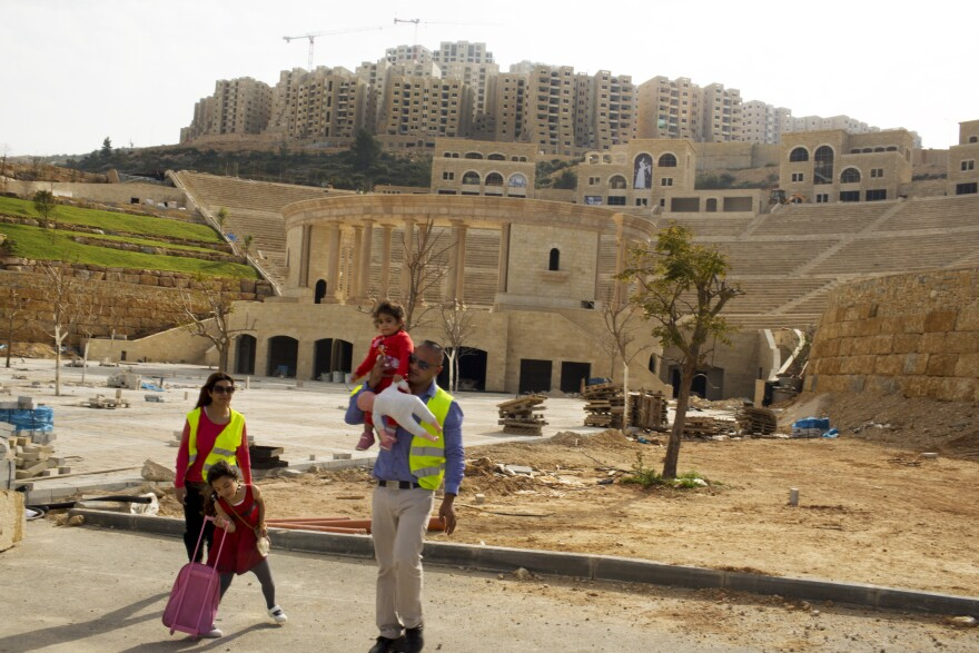 A Palestinian couple walks by an amphitheater under construction in Rawabi, a Palestinian real estate development in the West Bank. The couple lives nearby in East Jerusalem and says they are looking to buy in Rawabi as an investment or as a vacation home.
