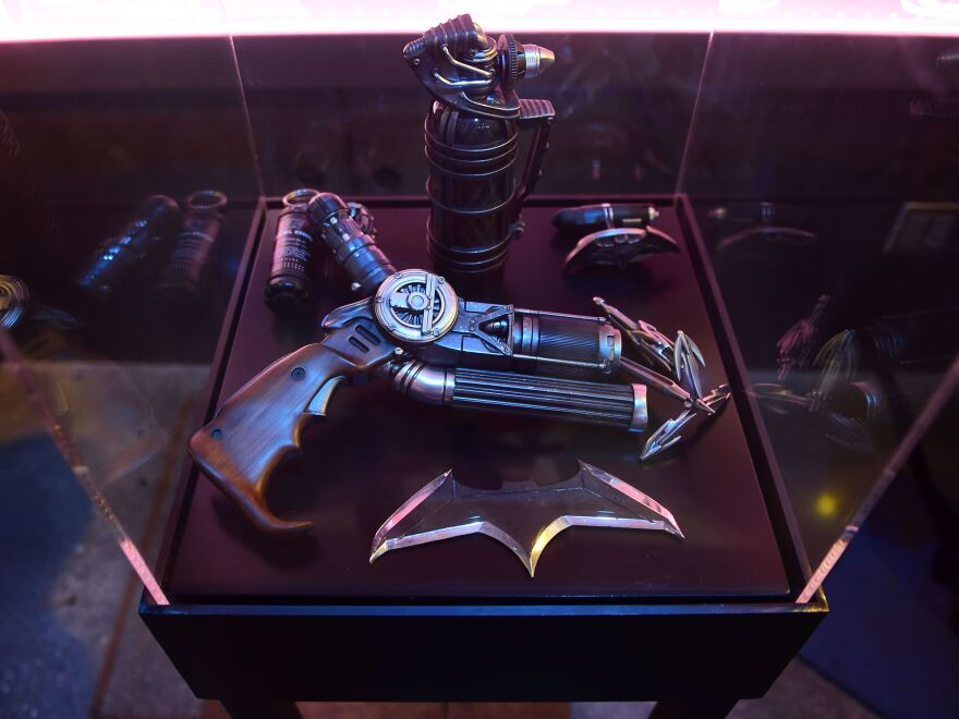 Batman's gun from <em>Batman v Superman</em> is displayed with a batarang and other weapons.