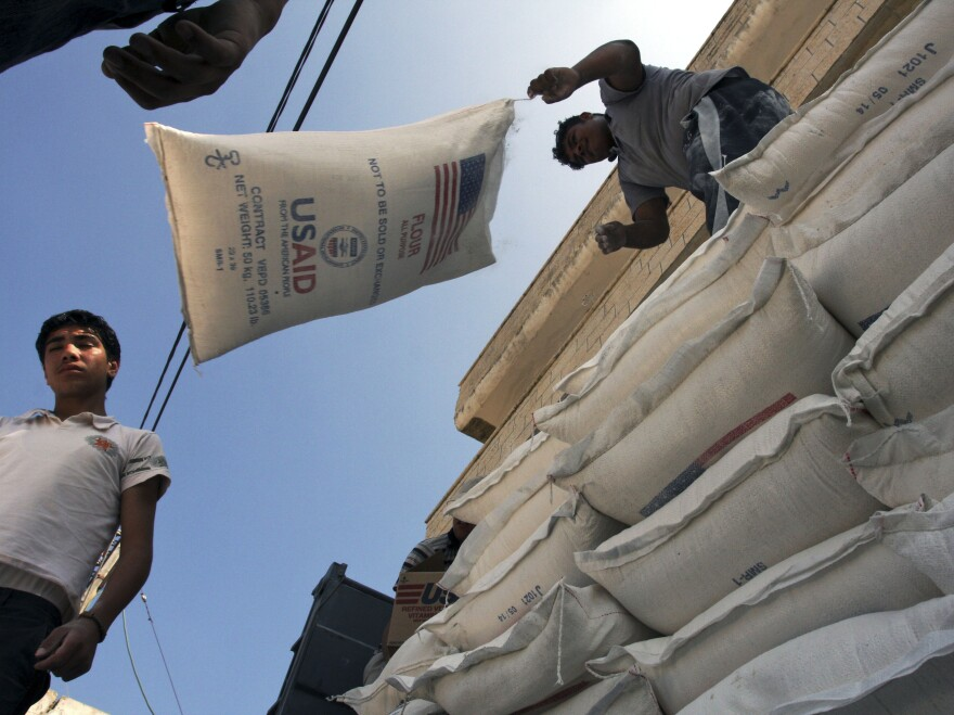 Palestinians unload bags of flour donated by USAID, or the United States Agency for International Development, at a depot in the West Bank village of Anin in 2008.