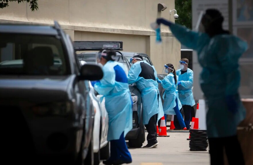 Health care workers collect coronavirus tests at a drive-thru site in the Fifth Ward in Houston.