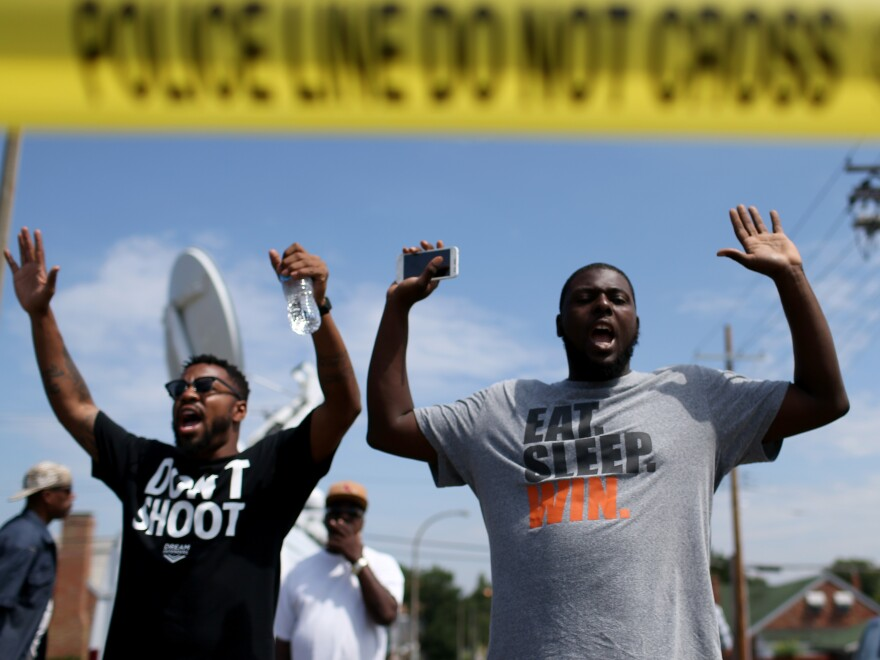 """The shooting of Michael Brown in Ferguson, Mo., also led to a series of protests. Many of them, like this protest on Aug. 19, featured people raising their arms and chanting, """"Hands up, don't shoot."""" But interactions between police and protesters were more tense — and sometimes violent — than in New York."""