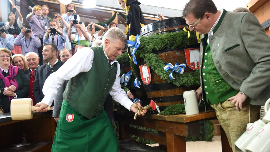 """Munich's Mayor Dieter Reiter uses a wooden hammer to pound a tap into the first Oktoberfest beer barrel. """"It is not most important mayoral job, but it is the most watched,"""" says Christoph Deumling."""