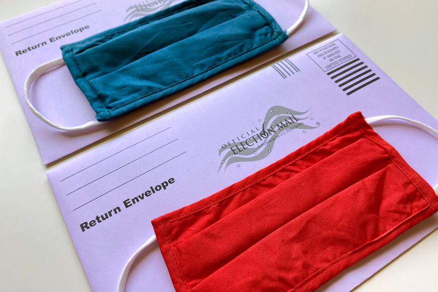 Two voting envelopes are on a table. One has a blue face mask on top of it and the other has a red one.
