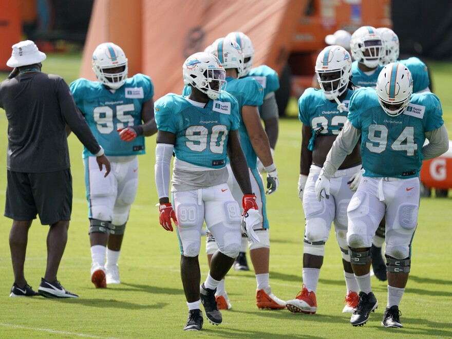 Players for the Miami Dolphins take a break between practice drills during training camp last Friday. When the regular season begins, they'll be playing in front of a smaller-than-normal crowd due to coronavirus restrictions.