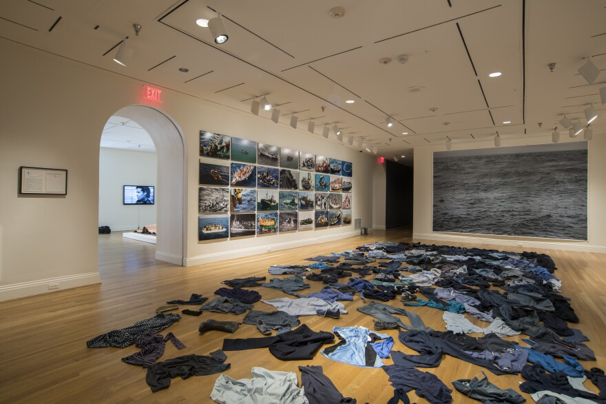 Kader Attia strews second-hand clothing on the floor for the installation <em>La Mer Morte (The Dead Sea).</em>