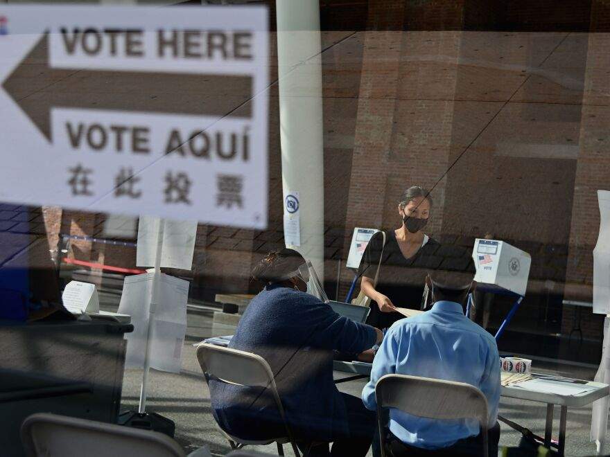 Many people who normally take on jobs as poll workers are in higher-risk groups for the coronavirus, leading to fears of a widespread shortage of poll workers. Here, New York City Board of Election employees and volunteers help voters at the Brooklyn Museum polling site during the New York Democratic presidential primary in June.