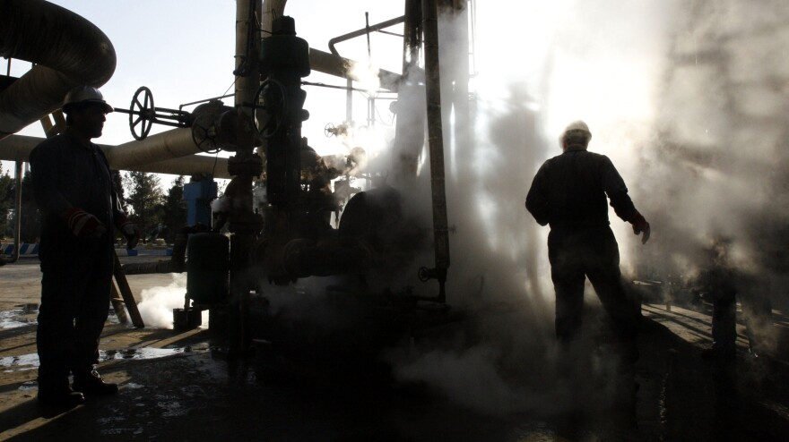 Iranian workers make repairs to a unit at Tehran's oil refinery in November 2007. It's estimated that a Western oil embargo is costing Iran about $4.5 billion each month in lost revenue.