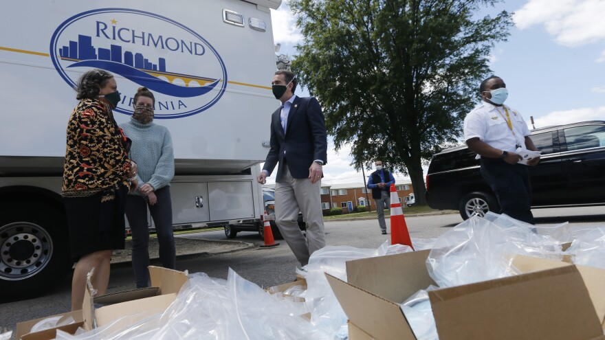 Virginia Gov. Ralph Northam (center) walks past boxes of personal protective equipment that volunteers plan to distribute Tuesday at an event in Richmond. Northam is doing a phased reopening in parts of the state outside the Washington, D.C., suburbs.
