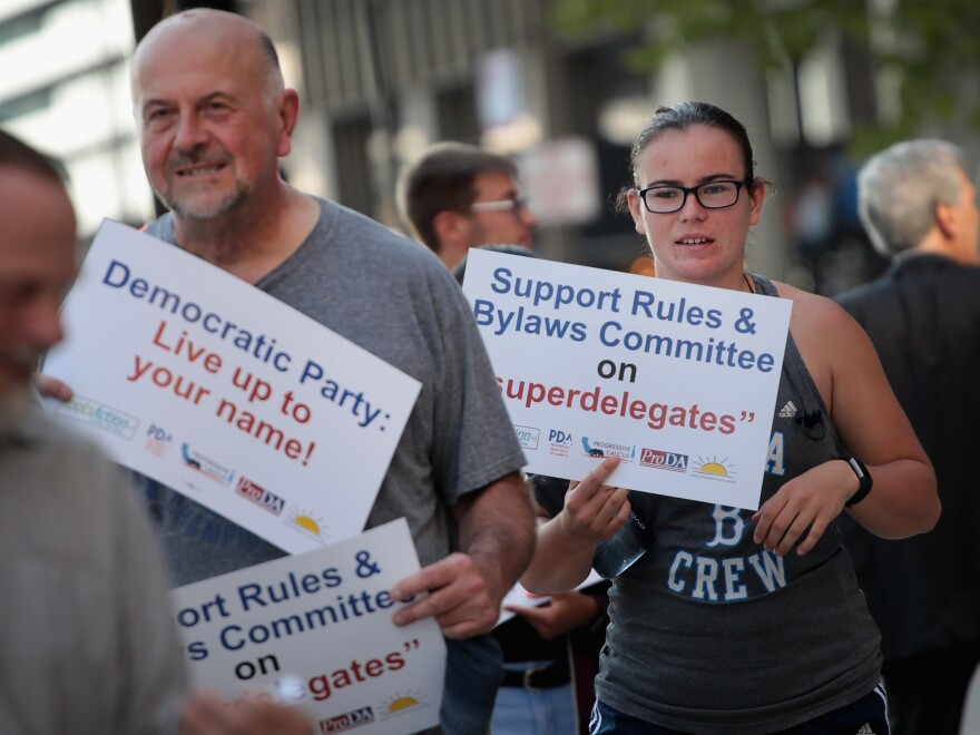"Demonstrators gather outside the Democratic National Committee's summer meeting to protest the use of ""superdelegates"" in the party's presidential nomination process. The DNC voted to drastically reduce their role this weekend."