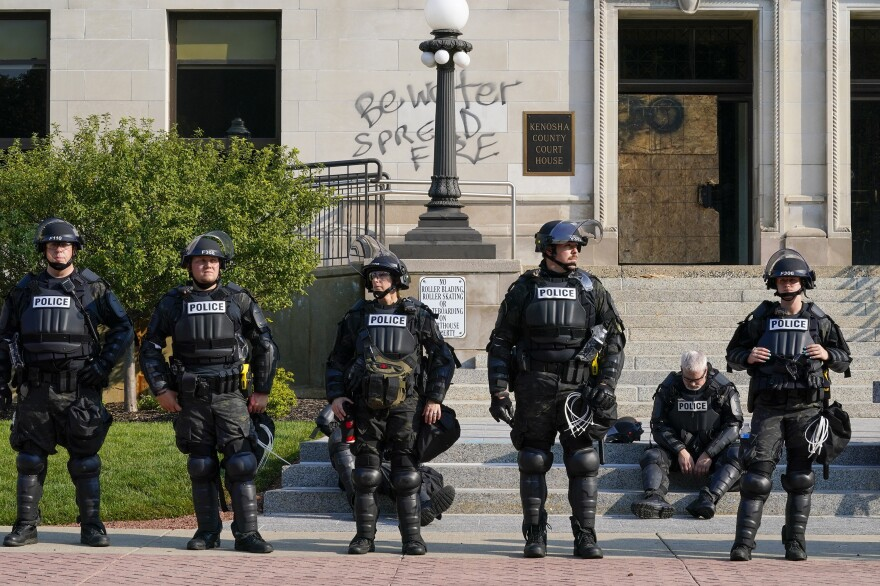 Police in riot gear stand outside the Kenosha County Courthouse on Monday in Kenosha.