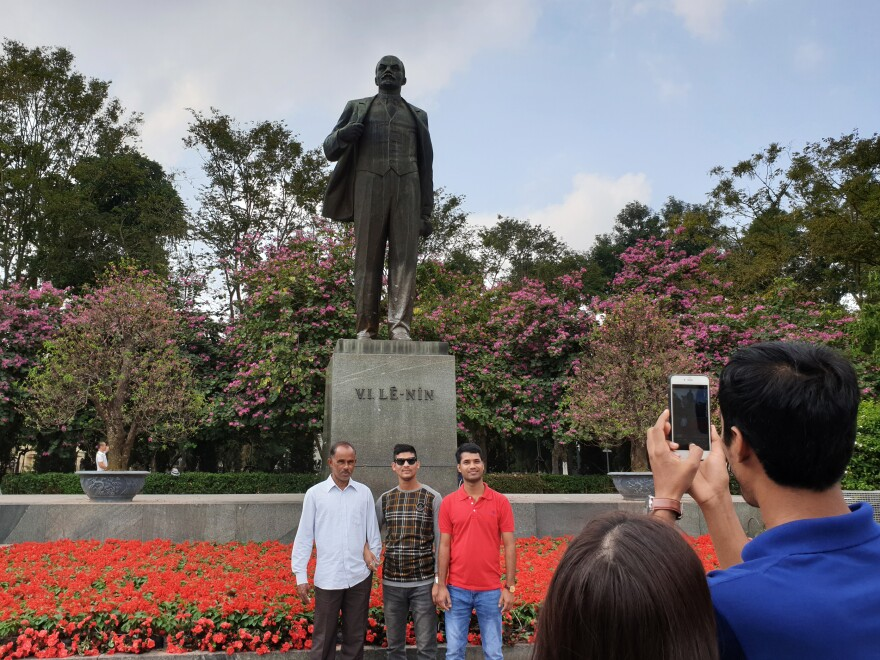 Tourists in Hanoi pose for a photo in front of a statue of Russian Communist Party founder and Soviet leader Vladimir Lenin.