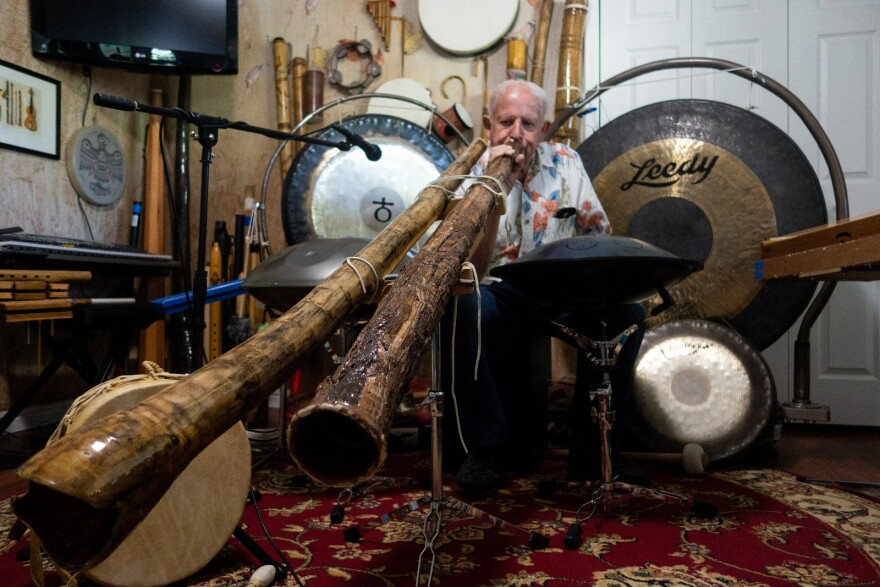 An older man plays the didgeridoo in a basement filled with instruments.