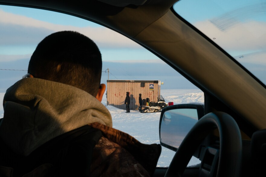 People wait for a plane to arrive at the airstrip in Toksook Bay.