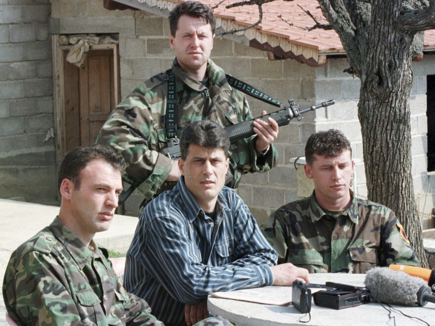 In a file photo from 1999, Hashim Thaci, center, head of the Kosovo Albanian negotiation team and head of the Kosovo Liberation Army political directorate, addresses a news conference in a secret location in central Kosovo.