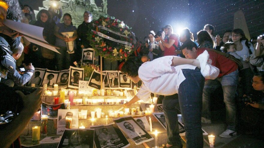 A woman lights a candle during a tribute to slain Mexican journalists at the Monument of Independence in Mexico City on May 5. The vigil took place to protest violence against the press after the brutal murders of four journalists in Veracruz state.