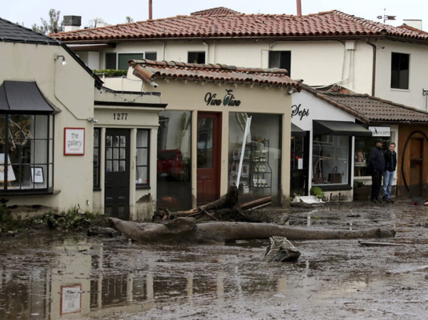 Debris and mud cover the street in front of shops in Montecito, Calif., Tuesday after heavy rain brought deadly flooding to the region.
