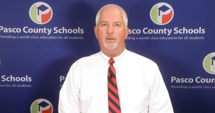 a screenshot of Pasco superintendent Kurt Browning in a white shirt and red tie