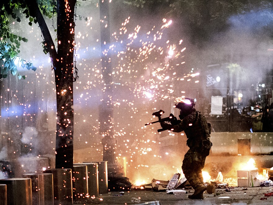 A federal officer fires crowd control munitions at Black Lives Matter protesters at the Mark O. Hatfield United States Courthouse on Friday in Portland, Ore.