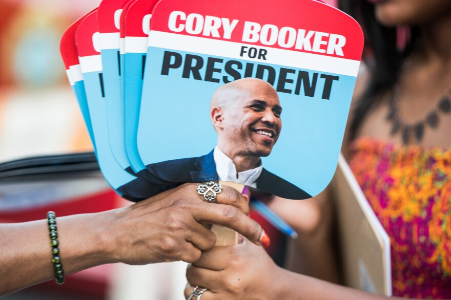 Supporters of Sen. Cory Booker share fans with the candidate's face. The 2020 presidential field, which includes at least three black candidates, is the most racially progressive ever.
