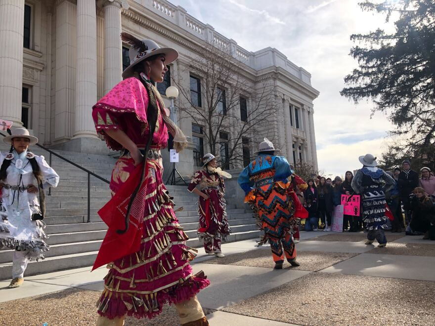 Women in bright dresses with pieces of metal sewn on dance in front of a courthouse
