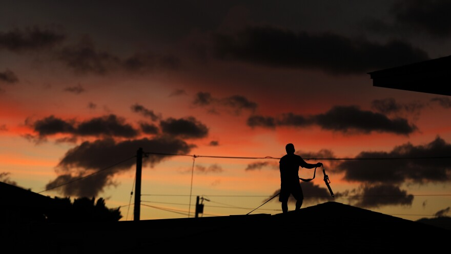 Jay Kitashima lashes down the roof of his home in preparation for Hurricane Lane on Wednesday along Ewa Beach in Honolulu.