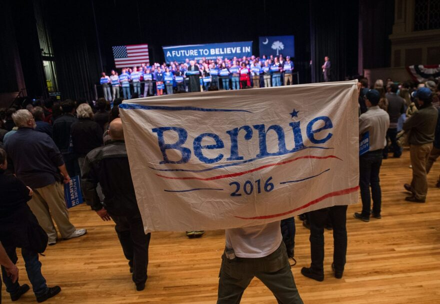 A supporter of Democratic presidential candidate Bernie Sanders holds up a sign as Sanders addresses a rally at the Township Auditorium in Columbia, South Carolina.