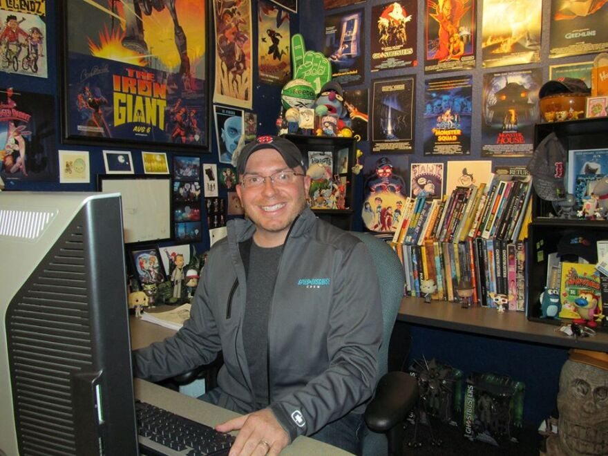 A photo of a man sitting at a desk. Movie posters are hung behind his desk.