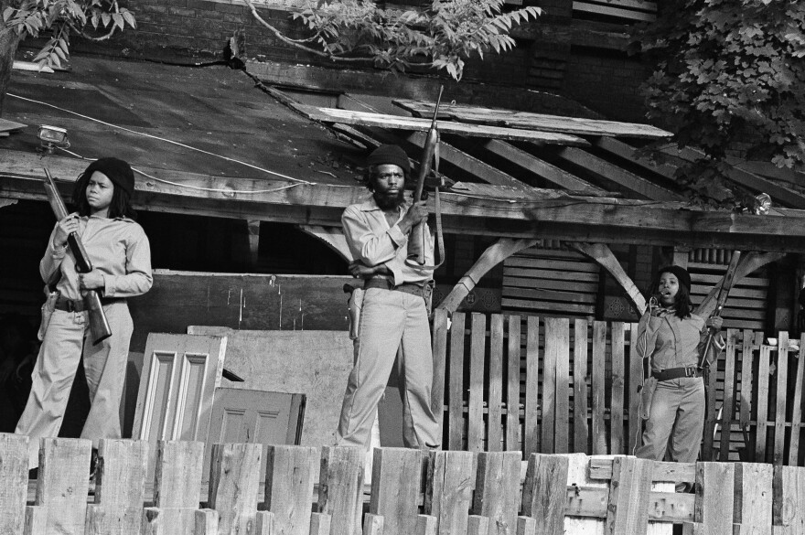 MOVE members hold sawed-off shotguns and automatic weapons as they stand in front of their barricaded headquarters on May 21, 1977.