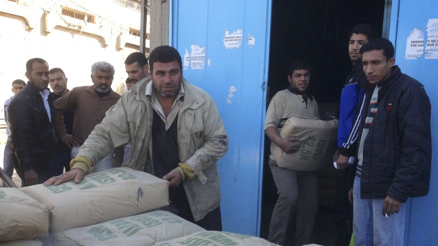 Men load bags of cement from a warehouse in Gaza. Under a complicated system meant to prevent militants from getting cement to use for tunnels, Palestinians must get approval from home inspectors to buy just one sack.