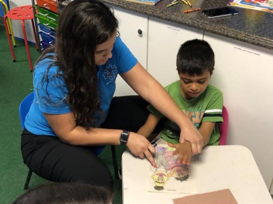 A behavior therapist works with a child who has autism spectrum disorder.