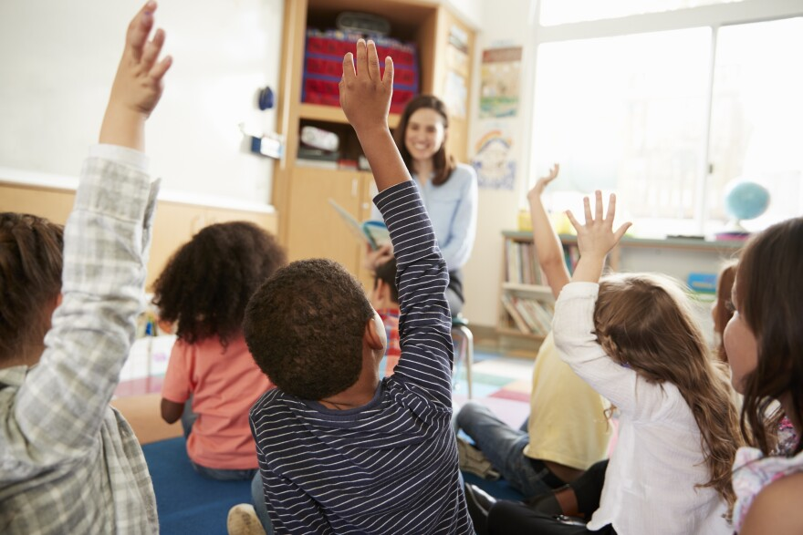 Photo of students raising their hands in a classroom.