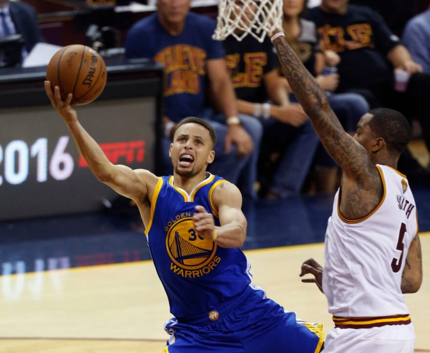 Golden State Warriors guard Stephen Curry (L) shoots over Cleveland Cavaliers guard J.R. Smith (R) during Game 6 of the NBA Finals in Cleveland, Ohio.