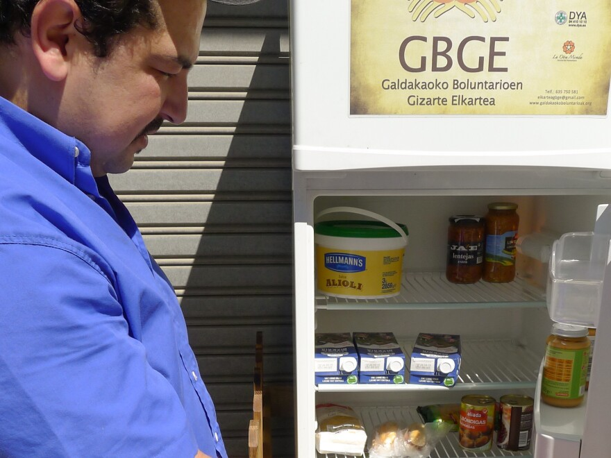 """Issam Massaoudi, an unemployed Moroccan immigrant, checks out what's inside the Solidarity Fridge. Massaoudi says money is tight for him, and it's """"amazing"""" to be able to help himself to healthy food from Galdakao's communal refrigerator."""